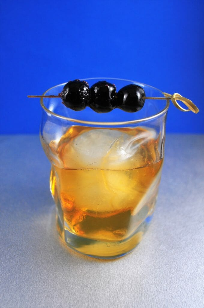 Cocktail in glass with large ice cube and three cherries on top