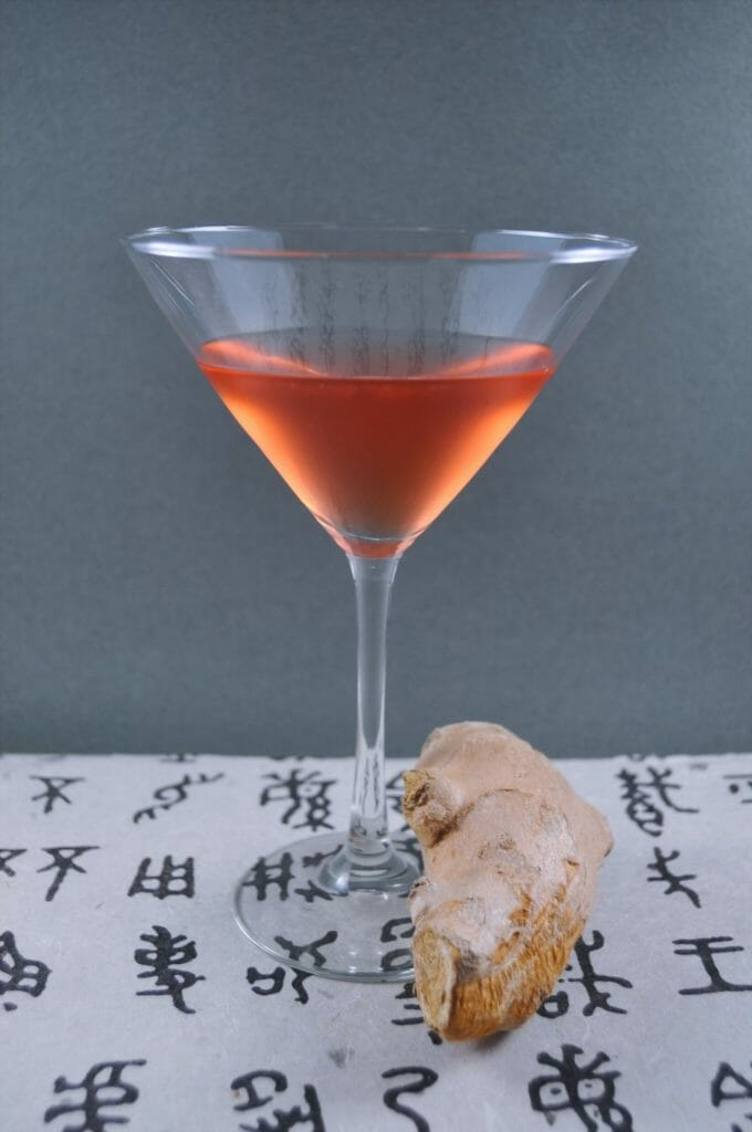 Cocktail next to a piece of ginger on top of print with Chinese characters