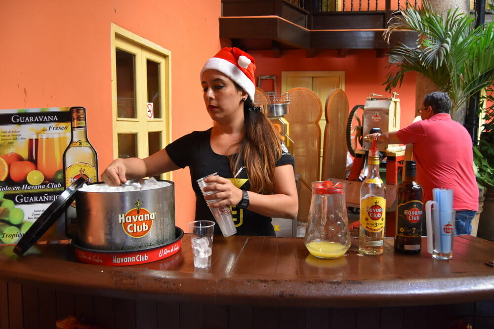 Girl wearing a Santa hat pouring a drink