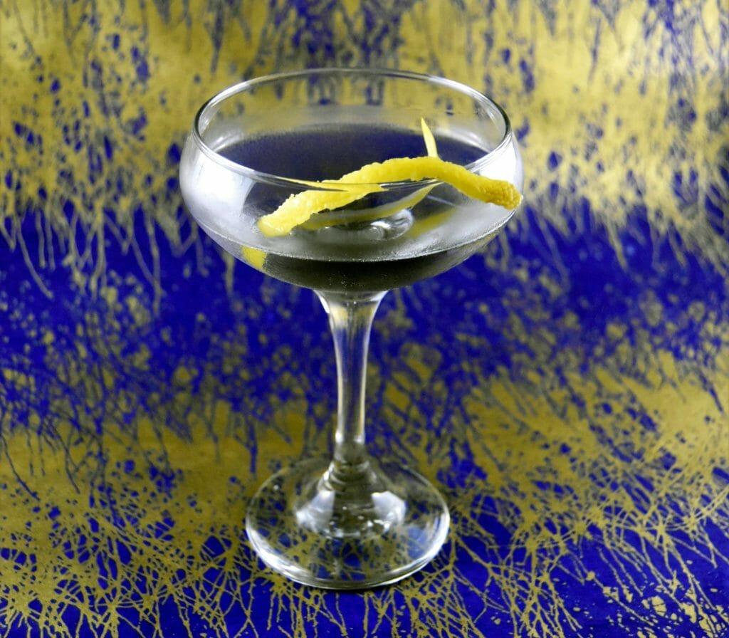 Cocktail with lemon twist in the middle against gold and blue backdrop
