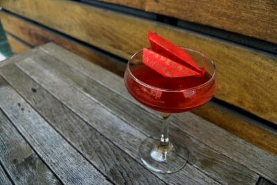Reddish drink in cocktail glass with red paper airplane on top of it