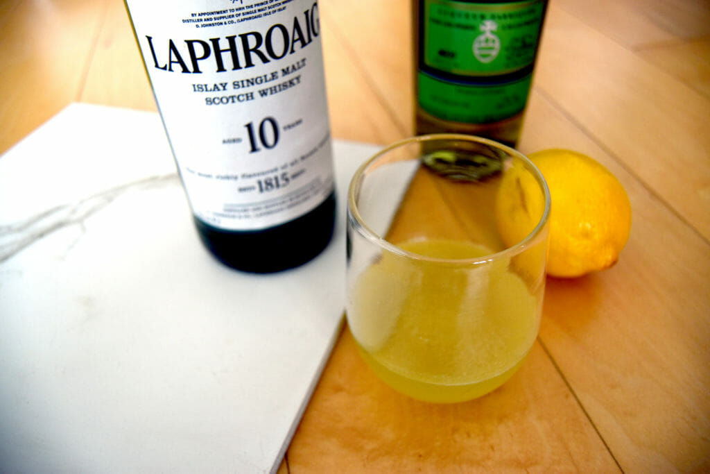 Cocktail in front of a bottle of Green Chartreuse and a bottle of Laphroaig