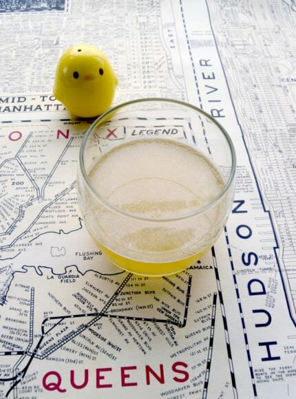 Cocktail sitting on map of NYC next to a small chicken