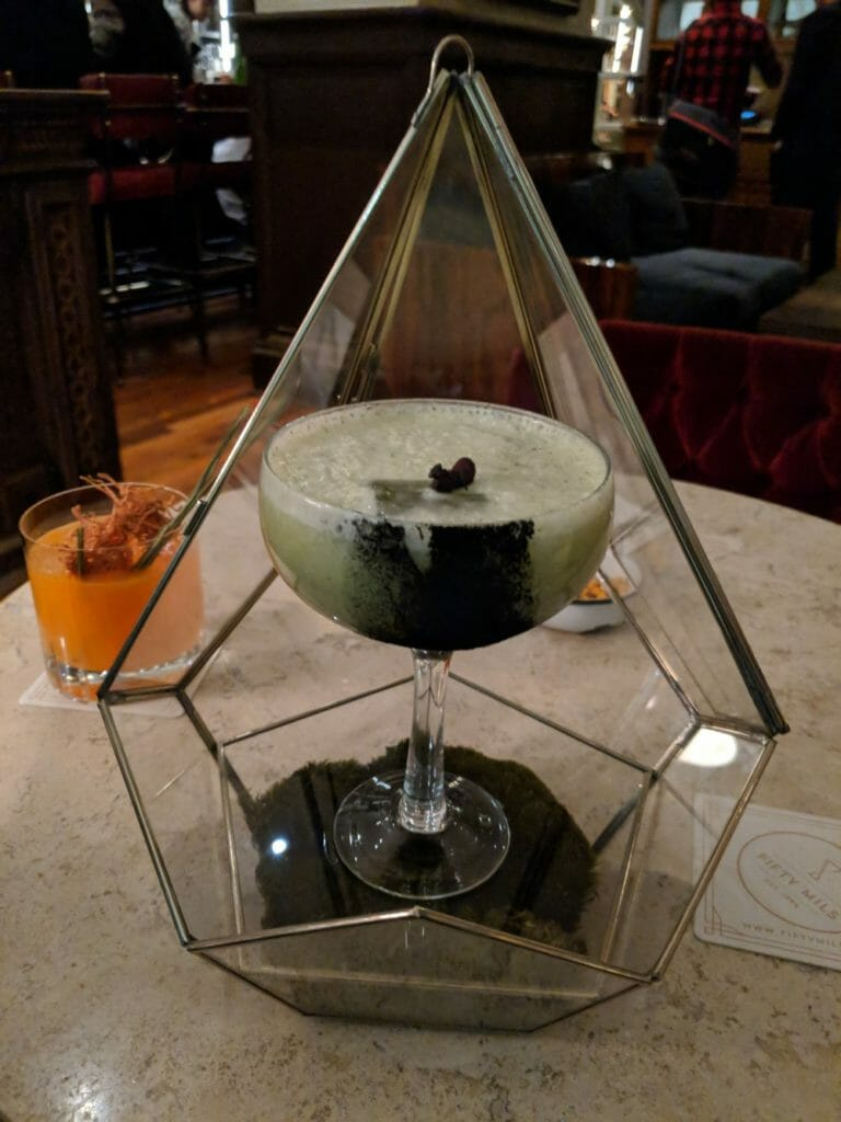 Cocktail in prism topped with ants with another orange cocktail behind it to the left