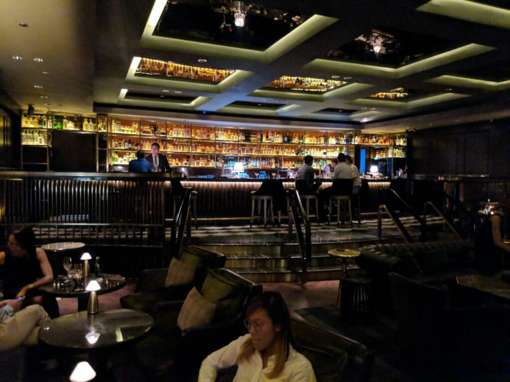 Bar with many bottles backlit with several people in front