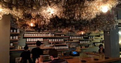 Bar with bee like texture and about a hundred identically labelled bottles