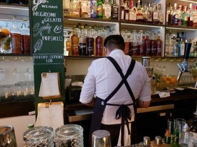 Bartender with his back turned in front of many bottles