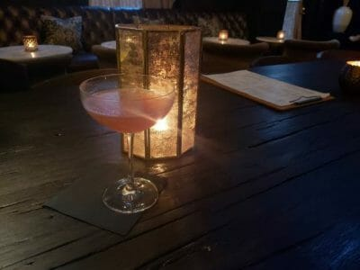 Cocktail with a light behind it and a menu to the right