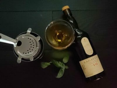 Cocktail next to a bottle of Lagavulin and a Hawthorne strainer