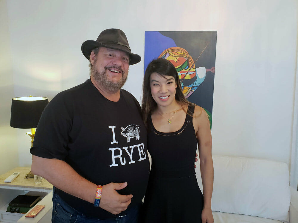 Man next to a woman with a painting behind them