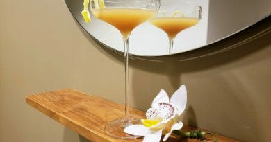 Cocktail in front of a mirror with a lemon garnish, the mirror reflects the cocktail