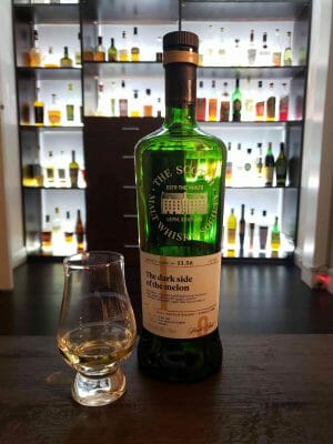 Whisky glass next to green bottle in front of well lit bar
