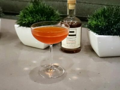 Cocktail in front of bottle of whisky and two plants
