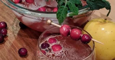 Glass topped with cranberries next to bowl of brown colored liquid
