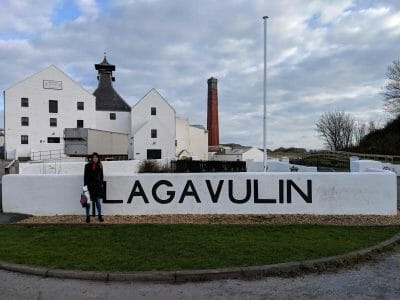 Woman in front of wall next to Lagavulin sign with buildings behind