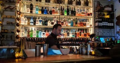Bartender in front of bar with many bottles