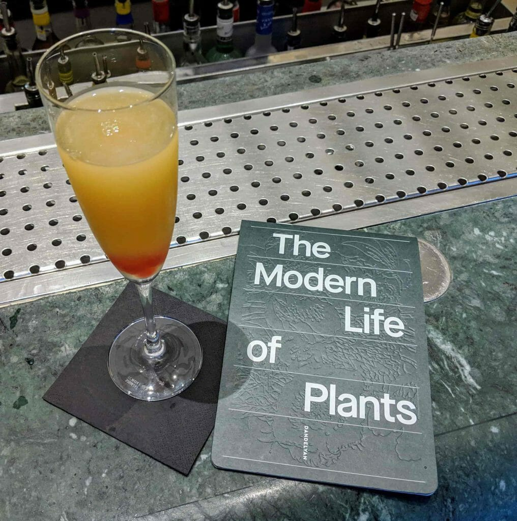 Glass filled with orange liquid next to book reading The Modern Life of Plants