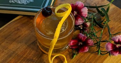 Cocktail with lemon twist and flower garnish