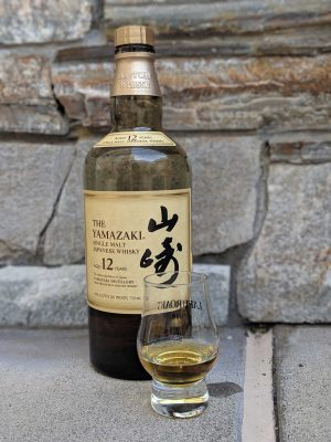 Bottle of Yamazaki 12 whisky with a glass containing whisky in front of it and stones behind