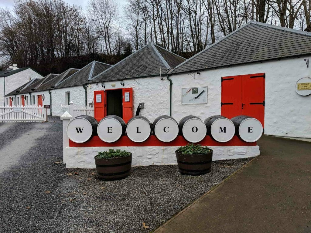 Several white barns with red doors and barrels that spell out welcome