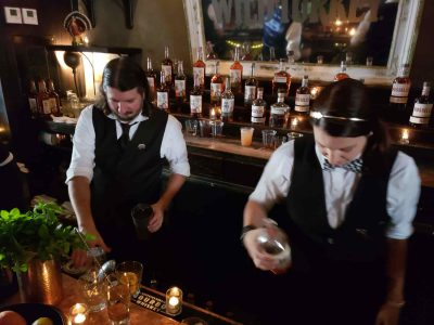 Men making cocktails in front of many bottles of whiskey