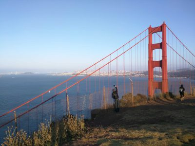Two people taking pictures of the Golden Gate Brdige