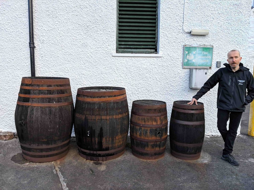 Man standing next to four whisky barrels of various sizes