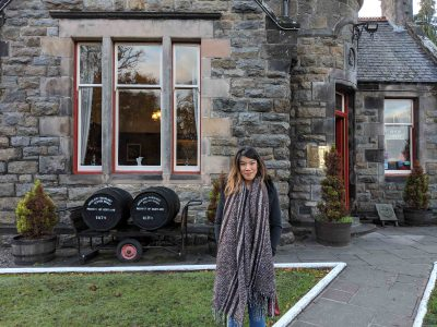 woman in front of old building with 2 barrels of whisky