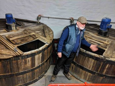 Man in front of wooden drums