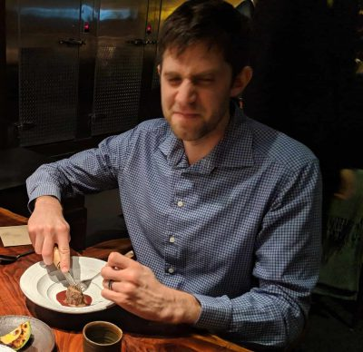 Man in striped shirt cutting into food