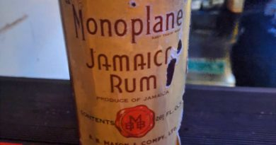 Bottle of rum on top of mat at bar
