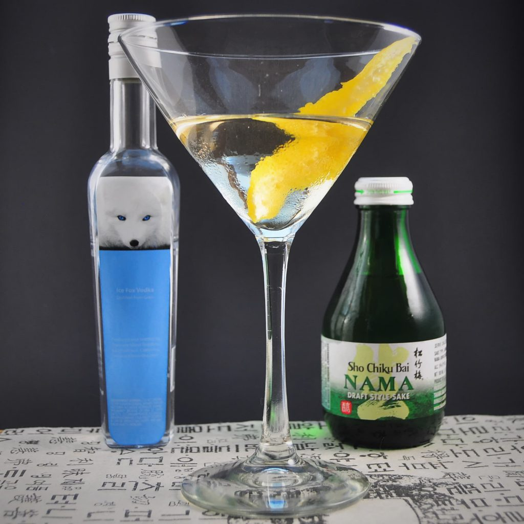 Cocktail in glass in front of small vodka bottle and sake bottle.