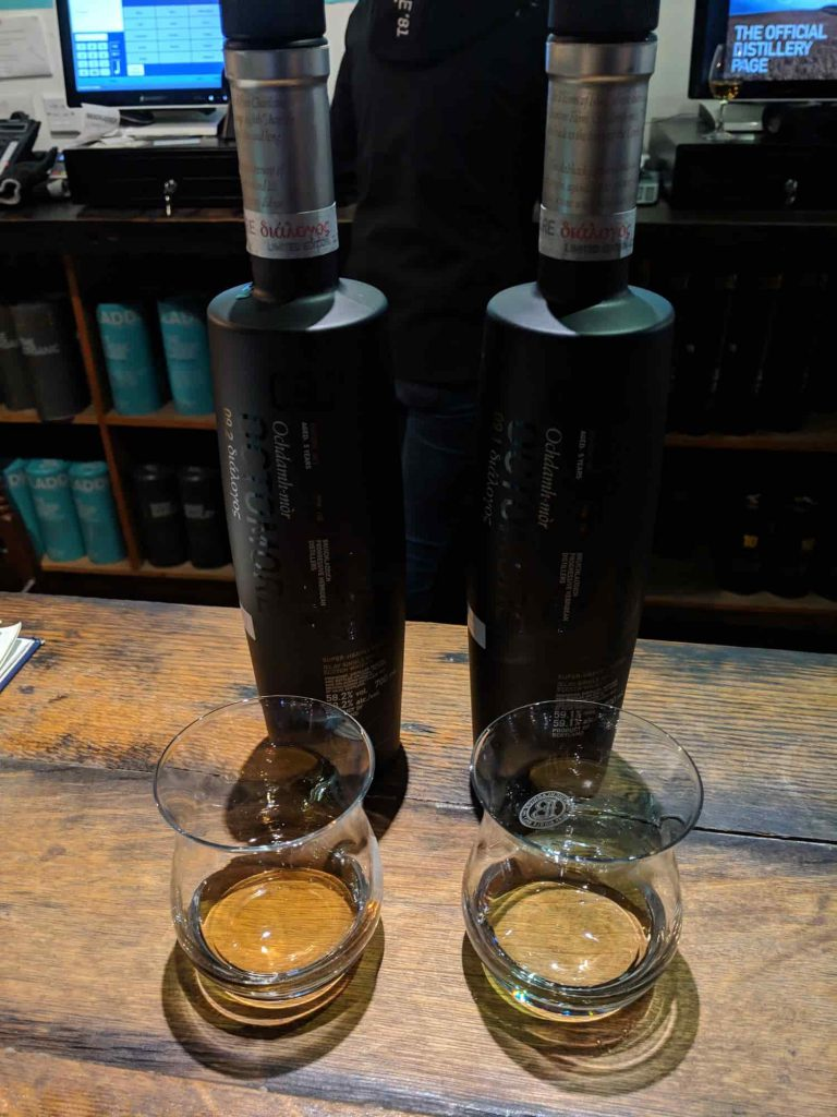 Two black bottles of whisky in front of tasting glasses