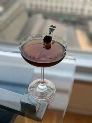 Red Eye Cocktail on top of glass surface with toothpick