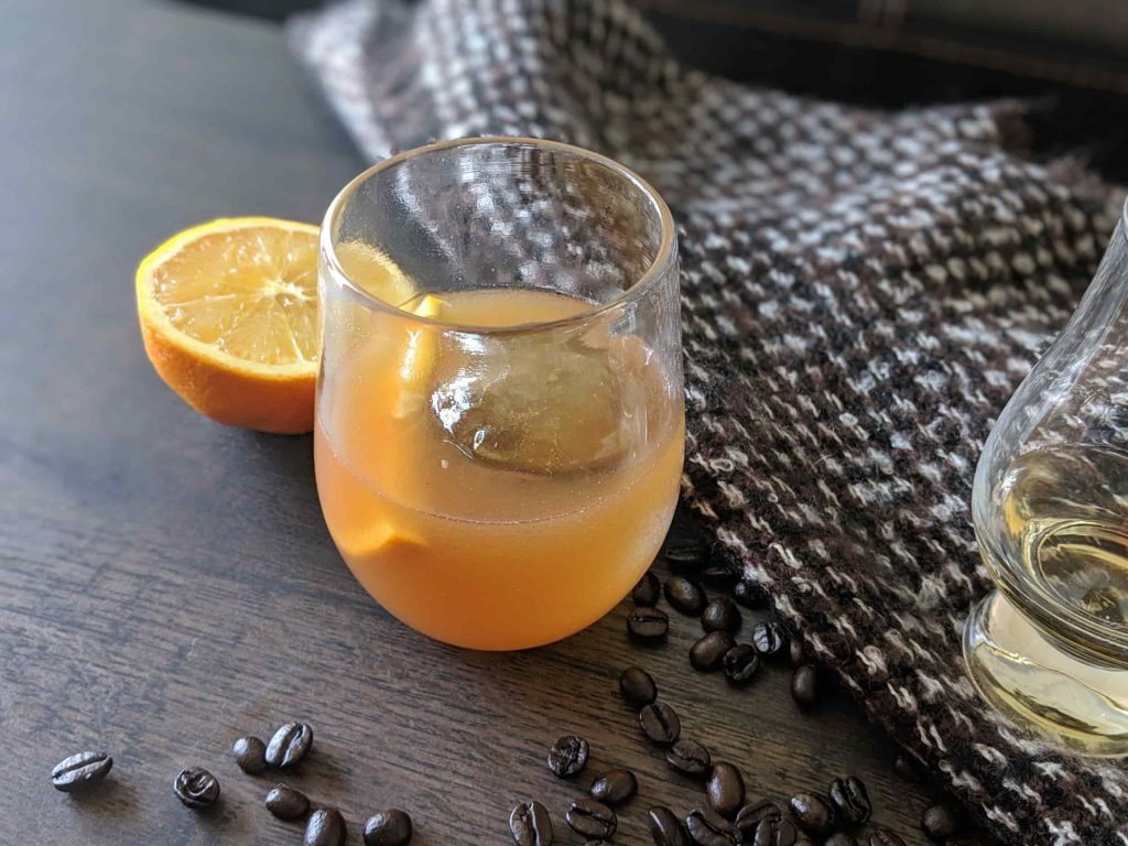 Cocktail in front of orange with many coffee beans