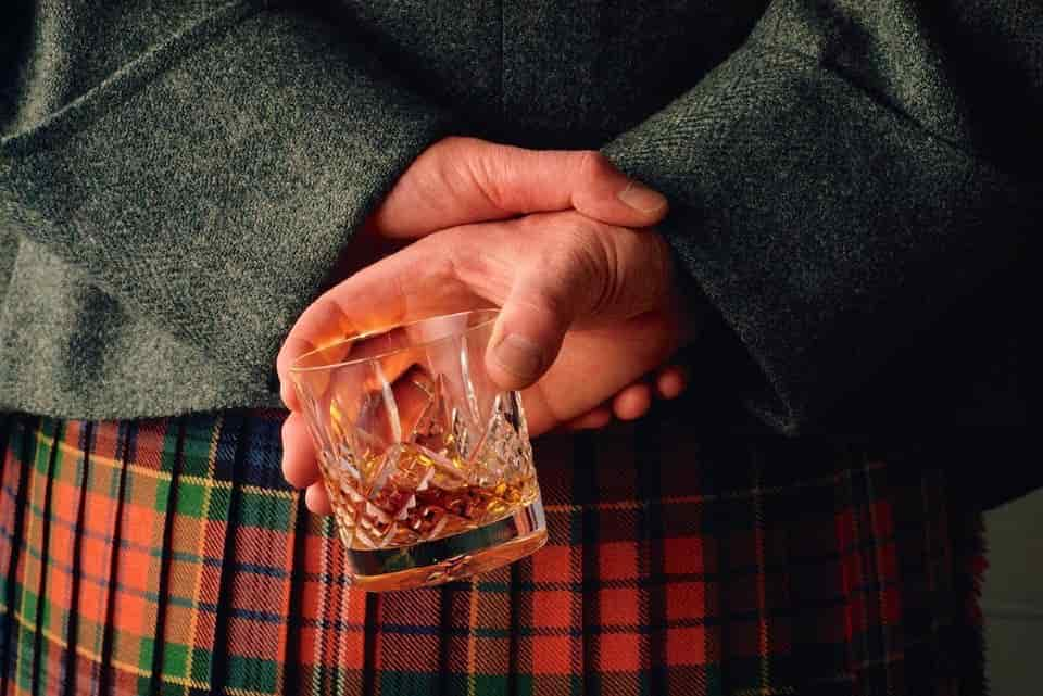 Man wearing kilt holding rocks glass containing whisky