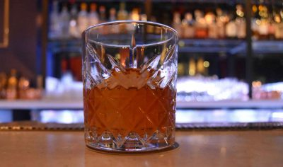 Old fashioned glass containing cocktail with giant rock
