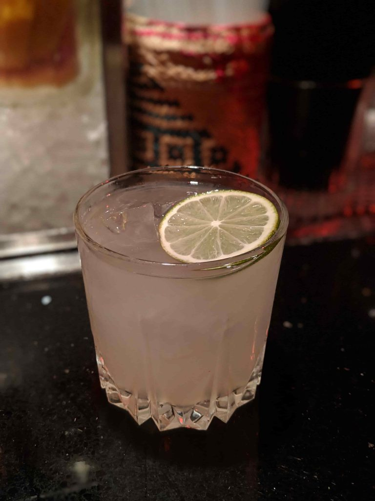 Cocktail topped with lime wedge garnish