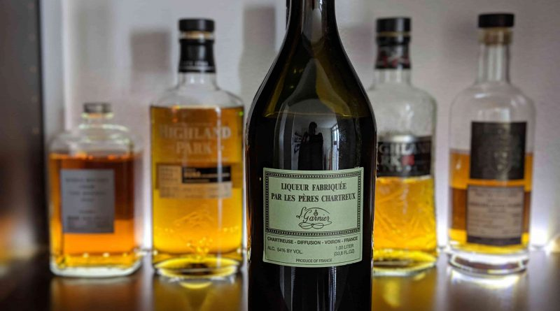 Bottle of green chartreuse in front of several other bottles