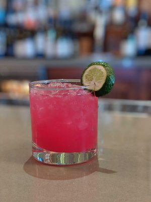 Bright pink drink with ice and a lime wheel garnish