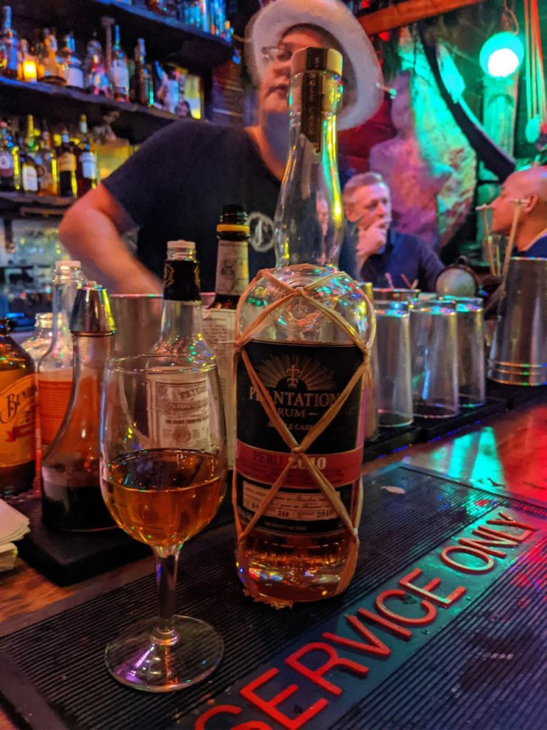Rum bottle next to rum glass in front of bartender with hat on.