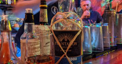 Plantation rum bottle next to glass on busy bar
